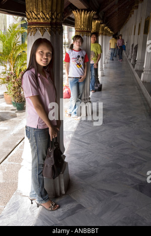 Thai tourists in the courtyard cloisters of Wat Phra Kaew, in the complex of The Grand Palace, Bangkok, Thailand - Stock Photo