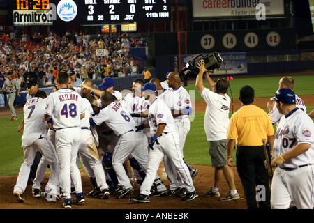 The New York Mets mob teammate Shawn Green after his extra-inning game winning home run at Shea Stadium on June - Stock Photo