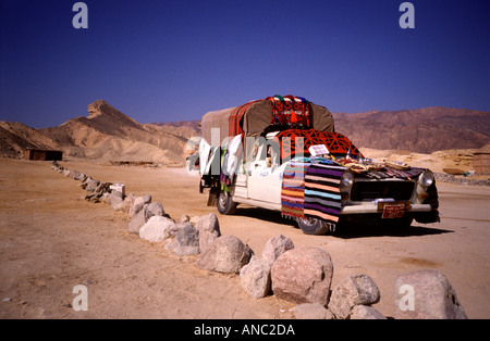 Traditional Bedouin rugs for sale covering an old Peugeot pick up car in Sinai desert near Dahab Egypt - Stock Photo