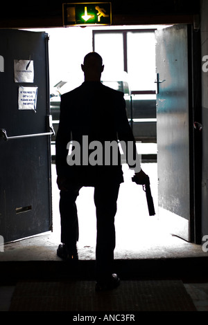 Silhouetted figure steps through doorway onto street with gun in hand - Stock Photo