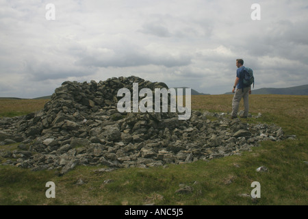 A man walking at the summit of Selside Pike above Swindale in the Eastern Fells of the Lake District, Cumbria, England - Stock Photo