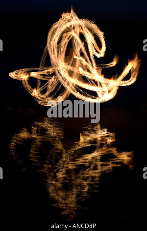 Man fire dancing on a rock in a lake in India - Stock Photo