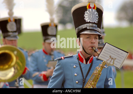 A saxophone player in a Swiss military band .The crest of Geneva on his headpiece. - Stock Photo