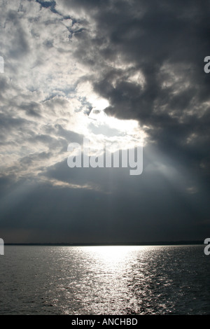Shaft of sunlight shining through clouds onto sea - Stock Photo