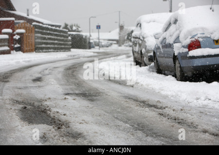 tyre tracks and car marks in the middle of the road on bend of snow covered street with ice slush and parked cars - Stock Photo