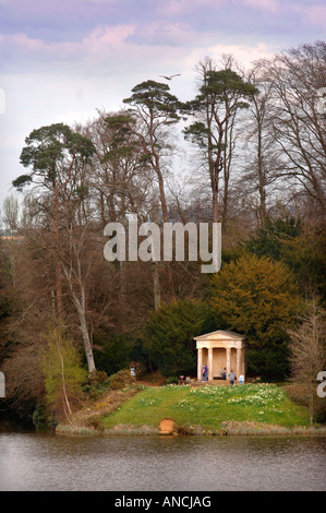 VISITORS IN THE GROUNDS OF BOWOOD HOUSE EXPLORE THE DORIC TEMPLE WHICH SITS BESIDE THE LAKE WILTSHIRE UK - Stock Photo