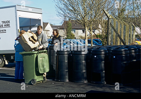 North Wales UK Two men wait to hand out black compost bins provided free by the local council - one man throwing - Stock Photo