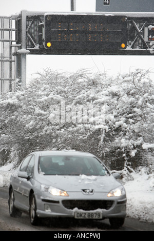 peugeot car with headlights on driving along treated road beside motorway warning sign - Stock Photo