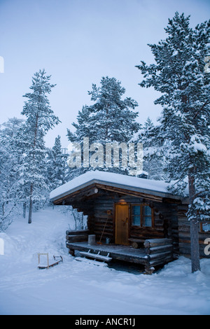 Log cabin holiday home at Kakslauttanen Igloo Village in Finland with sled/sledge by front door - Stock Photo