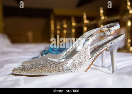 brides shoes on a bed - Stock Photo