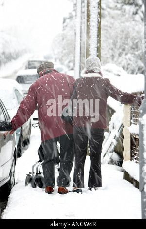 elderly infirm couple walking along footpath holding on for balance in heavy snowstorm - Stock Photo