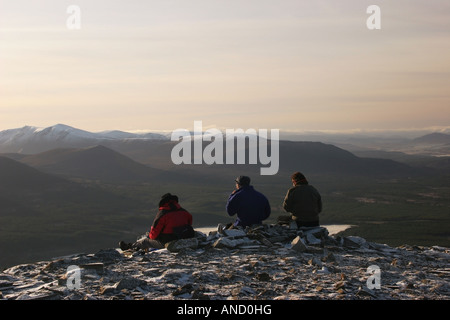 Three Walkers Enjoying the View Over Loch Morlich From the Summit of Meall a Bhuachaille Cairngorms Scotland in - Stock Photo