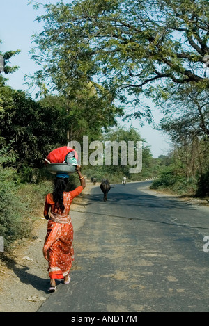 A woman carries goods on her head as she walks down a long road - Stock Photo