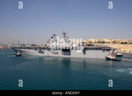 The amphibious assault ship USS Kearsarge is assisted by tugs as she berths in Malta's Grand Harbour - Stock Photo
