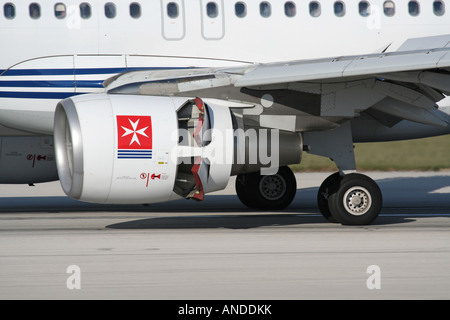Close-up of a CFM56 turbofan engine nacelle on an Air Malta Airbus A320 jet plane with thrust reversers activated - Stock Photo