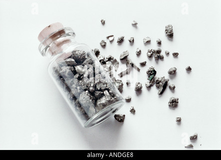 Silver mineral stone stone in and out in the small glass bottle gold fool jar still life object container abstract - Stock Photo