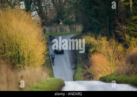 Car overtakes cyclists on country road near Burford United Kingdom - Stock Photo