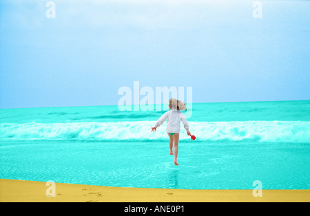 Young girl having fun running into the sea France - Stock Photo