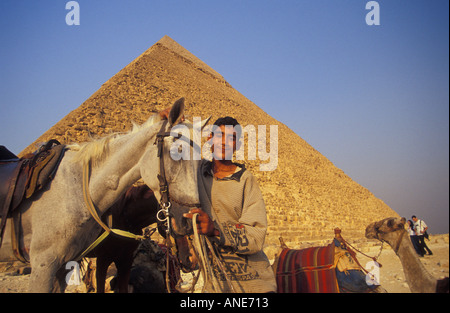 Egyptian Boy Offering Horse Ride in Front of the Pyramids in Giza (Egypt) - Stock Photo