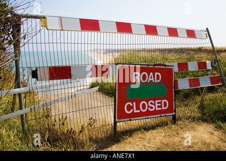 Road Closed sign in front of eroded shoreline road on Norfolk Coast United Kingdom - Stock Photo