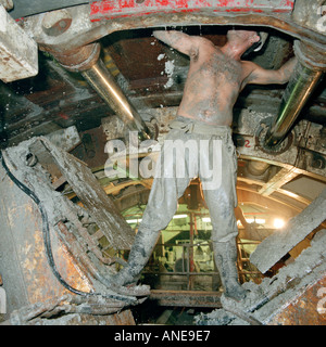 A Channel Tunnel engineer carries out essential maintenance on a huge undersea tunnel boring machine passing through - Stock Photo