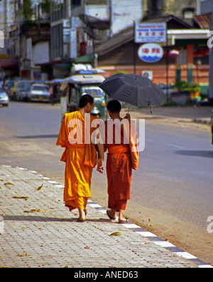 Pair of novices in colourful clothing walk streets of city centre shading under umbrella Luang Prabang Laos Southeast - Stock Photo
