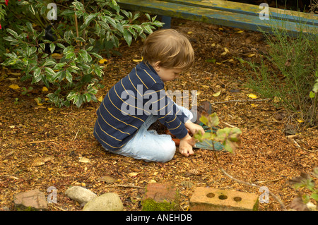 A cute baby boy toddler concentrating playing with a shape for Gardening tools for 3 year old