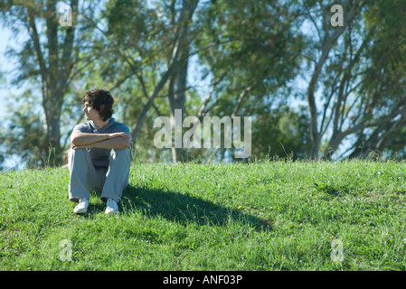 Teen boy sitting on grassy hill, relaxing - Stock Photo