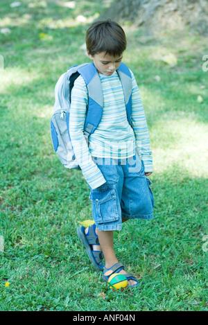 Boy walking across grass wearing backpack - Stock Photo
