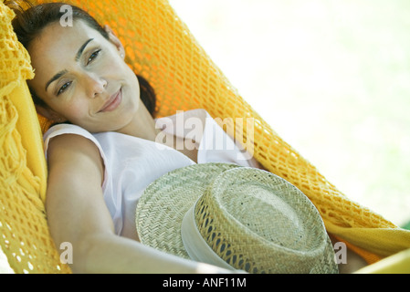 Woman lying in hammock, holding straw hat - Stock Photo