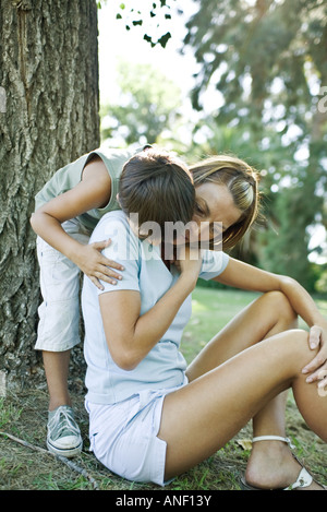 Mother and son outdoors, boy hugging mother from behind - Stock Photo