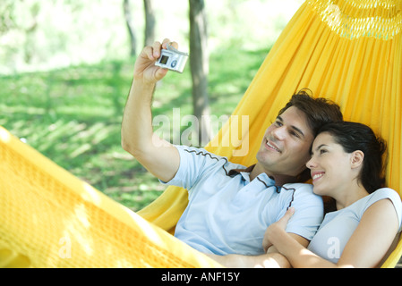 Couple lying in hammock together, man taking self-portrait with digital camera - Stock Photo