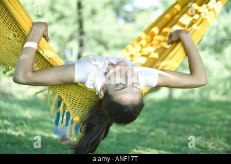 Woman lying in hammock, head hanging upside down - Stock Photo