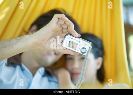 Couple lying in hammock together, man taking photo with digital camera - Stock Photo
