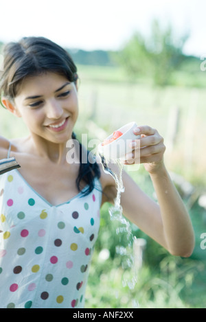 Young woman rinsing tomatoes in cup outdoors Stock Photo
