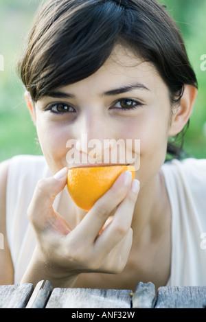 Woman eating slice of orange, smiling at camera, close-up - Stock Photo