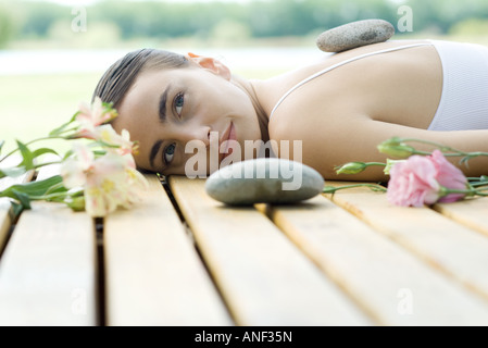 Woman lying on deck with hot stone on back surrounded by flowers and stones - Stock Photo