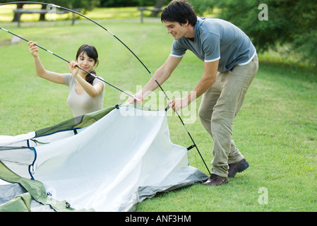 Young campers setting up tent - Stock Photo