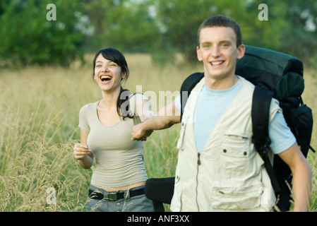 Young couple going for hike, man pulling woman toward him - Stock Photo