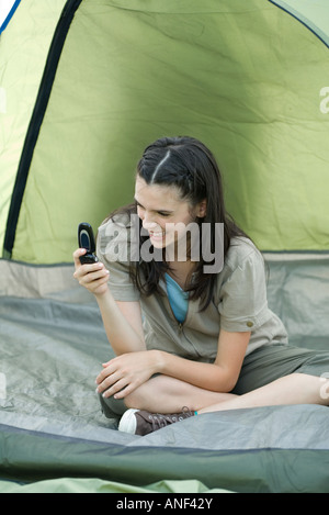 Teen girl sitting in tent, holding cell phone - Stock Photo