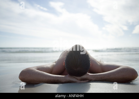 Young man lying on beach, hands behind head - Stock Photo
