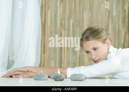 Woman lying on floor, looking at candles - Stock Photo