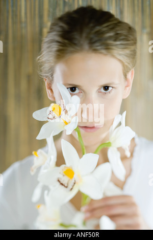 Woman looking through flowers, portrait - Stock Photo