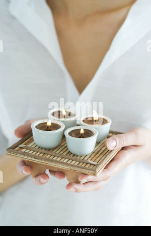 Woman holding tray of candles, close-up, cropped - Stock Photo
