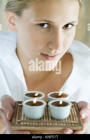 Woman holding up tray of candles, close-up - Stock Photo