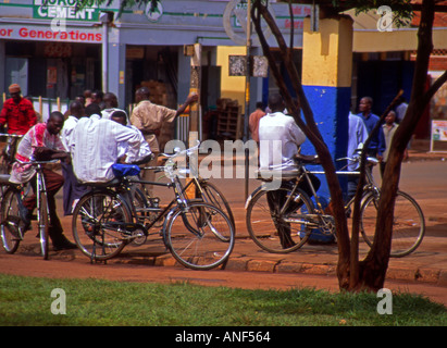 Group of young men sitting still on bicycles in busy city centre streets  resting & socialising Jinja Uganda East - Stock Photo