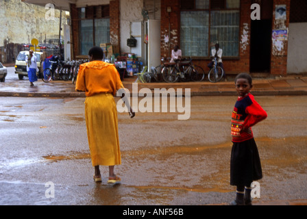 Mother & daughter girl in colourful clothing going about the streets of capital in a rainy day Kigali Rwanda East - Stock Photo