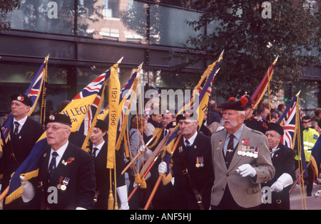 War veterans with medals and poppies from Royal British Legion marching with flags in Lord Mayors Show, City of - Stock Photo