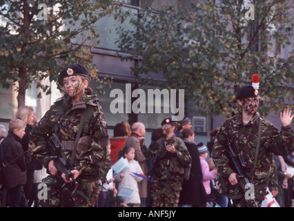 Young women army soldiers of British Armed Forces in camoflage fatigues and face paint with automatic weapons, London - Stock Photo