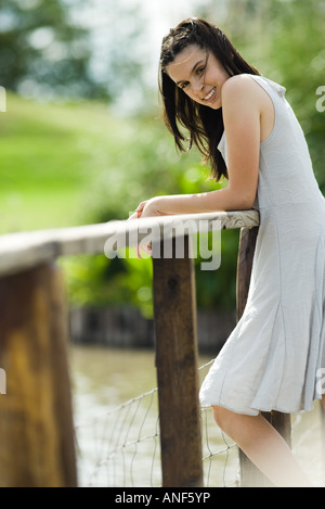 Teen girl leaning against wooden railing outdoors, smiling at camera - Stock Photo
